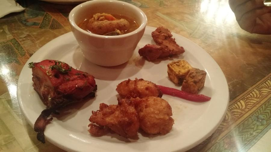 A dish of tandoori chicken, manchurian, paneer, and vada sambar as an appetizer