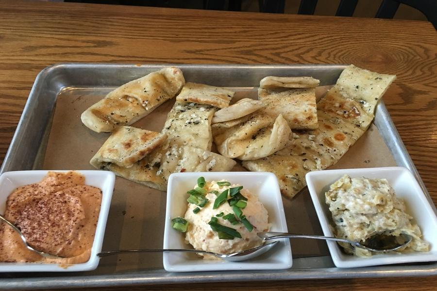 The crazy bread served with the three sauces, smoked tomato humus, Calabrian cheese spread, and artichoke mista.