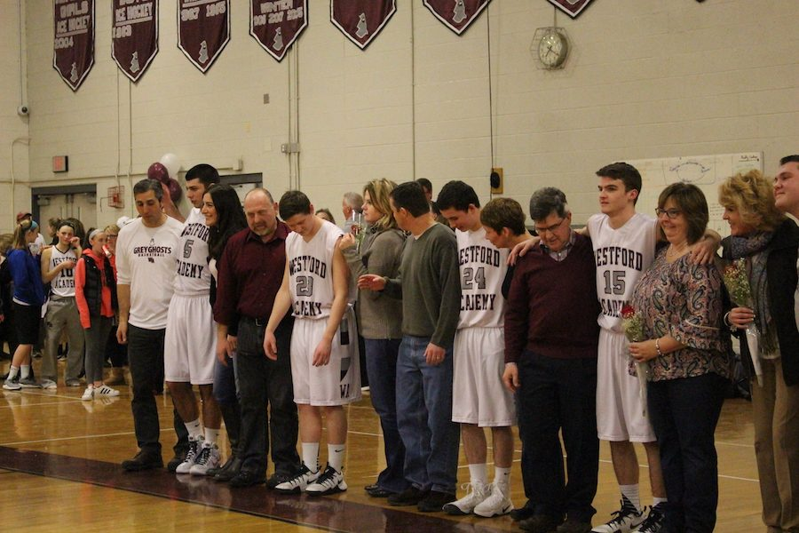 Senior+basketball+players+lining+up+with+their+parents+%0A