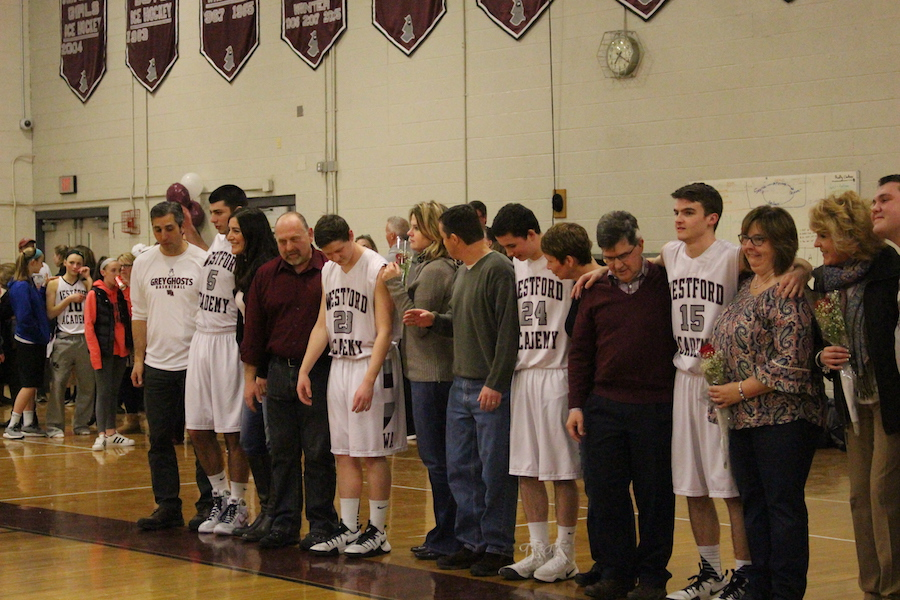 Senior basketball players lining up with their parents