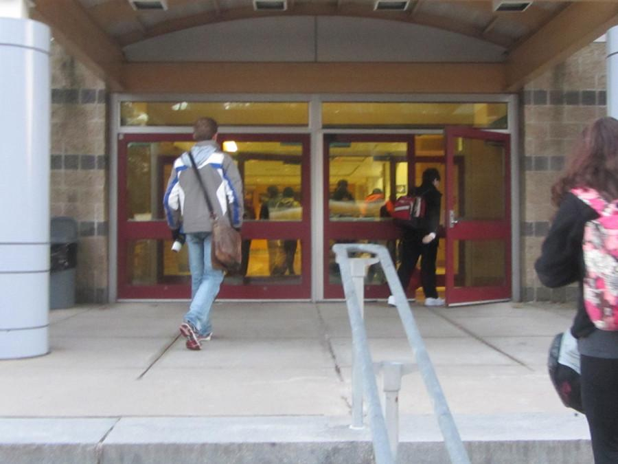 Students entering Westford Academy through doors that will soon feature heightened security measures.