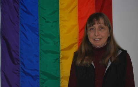 Susan Beers in her office, besides the GLBT flag.