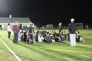 Seniors sit on the field after their game to protest the way their game ended