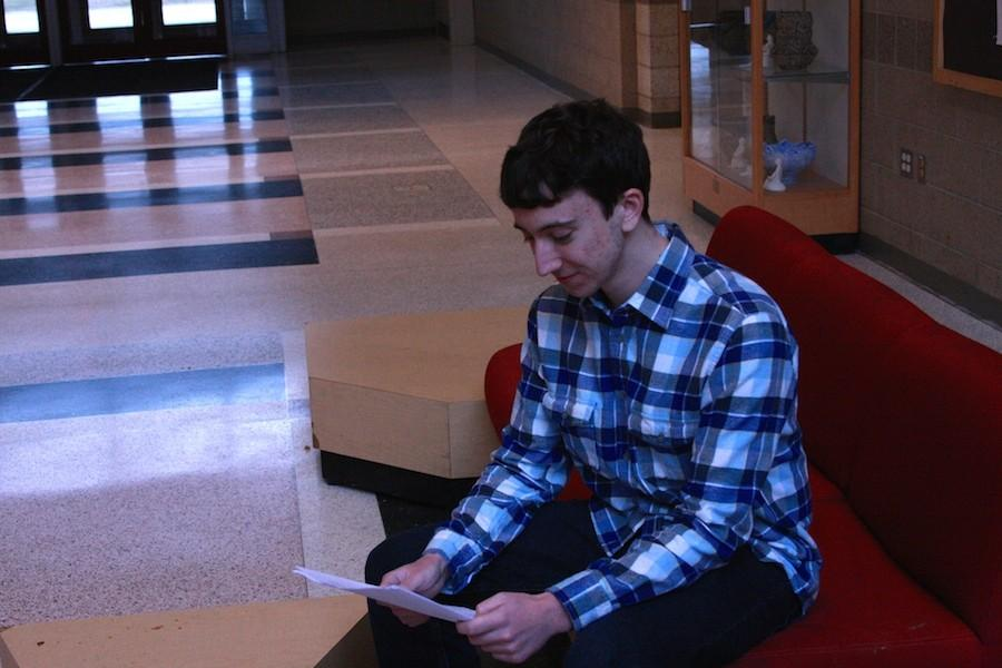 Senior Michael Colavita sitting down in the flag lobby, reviewing his petition.