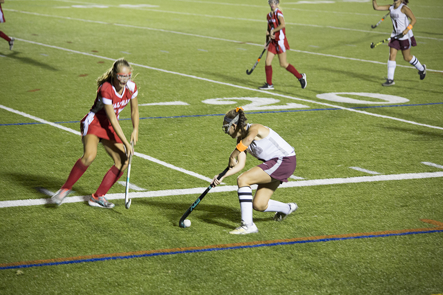Junior Hannah Keefe drags back the bal to avoid an incoming Waltham defender