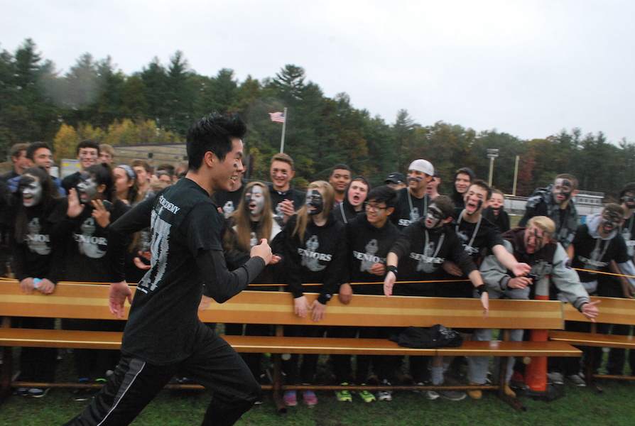 Senior+Athlete+high-fives+his+friends+while+taking+a+victory+run+along+the+crowd.