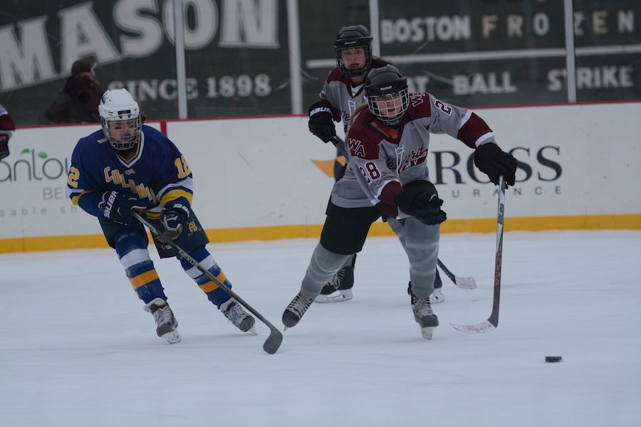Senior Colleen Ellis skates off with the puck, resisting AB defense.