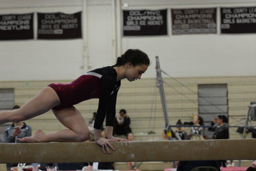 Senior Julia Vitto raises herself onto the balance beam.