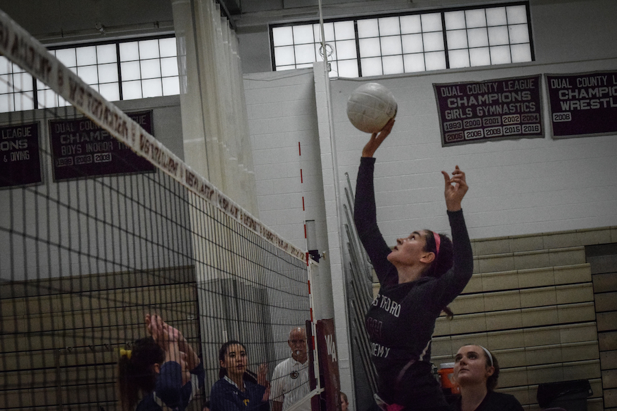 Middle Hitter Elise Sepe jumps to hit the ball right while her teammates and opponents watch in suspense.