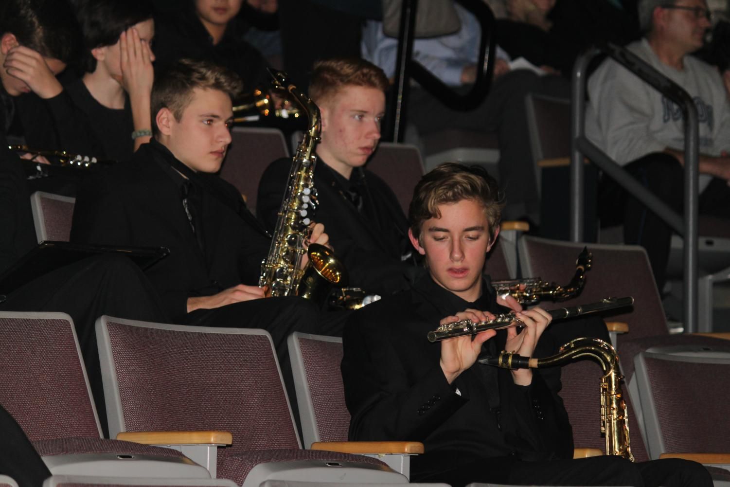 Senior+Tyler+Dillon+holds+a+flute+in+the+band+section+of+the+audience+after+conducting+a+song+onstage.