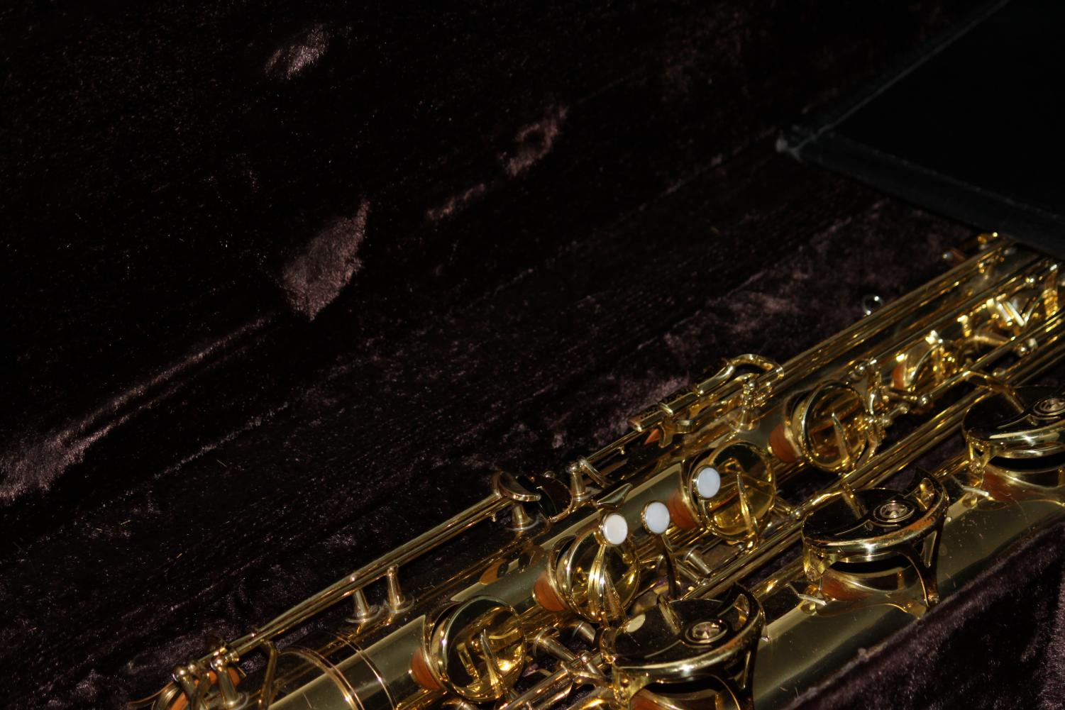 A+brass+saxophone+sitting+open+in+its+case+backstage