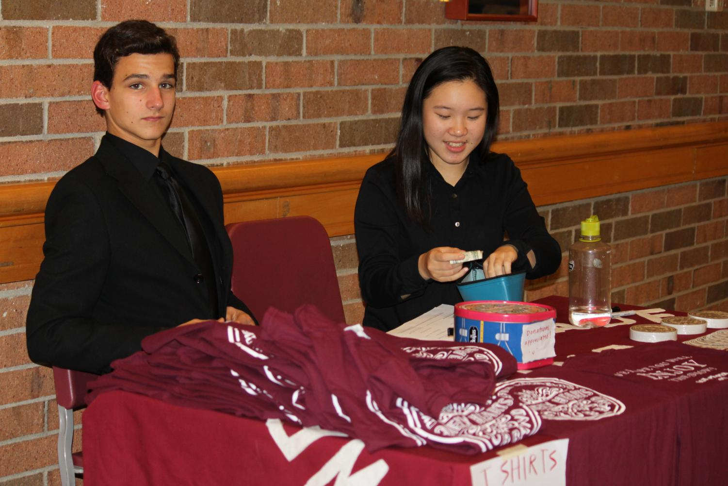 Junior+Christine+Ji+and+sophomore+Collin+Pickersgill+sell+stickers+and+t-shirts+to+raise+money.