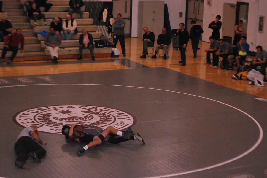 Sophmore Ian Njihia pins his opponent.