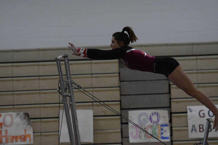 Senior+Jelina+Farrell+reaching+for+the+bar+as+she+practices+her+routine+before+the+meet