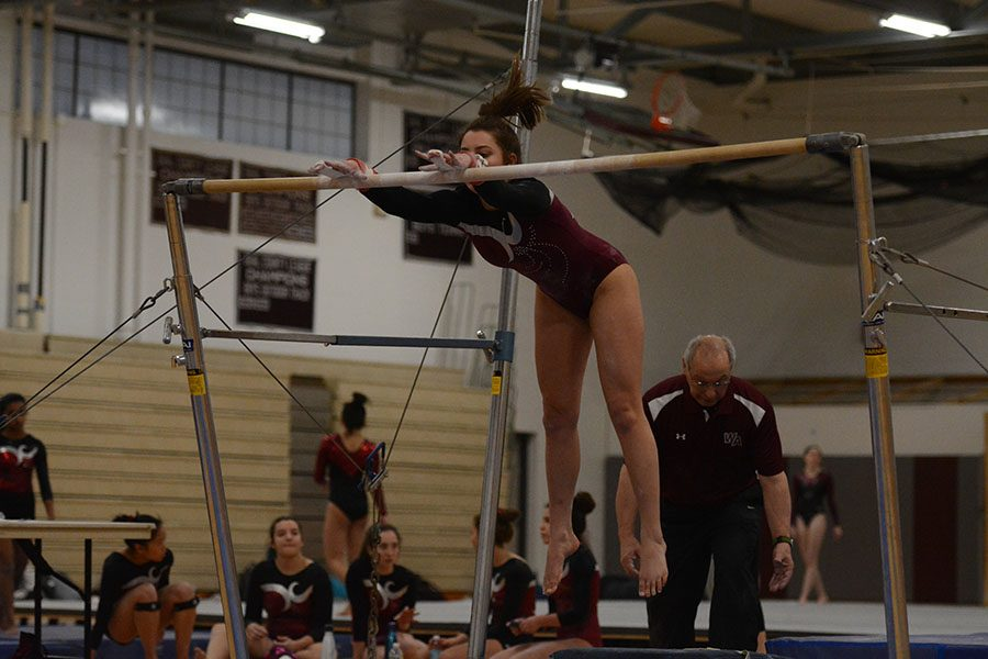 Senior Jelina Farrell, practicing her routine on the even bars.