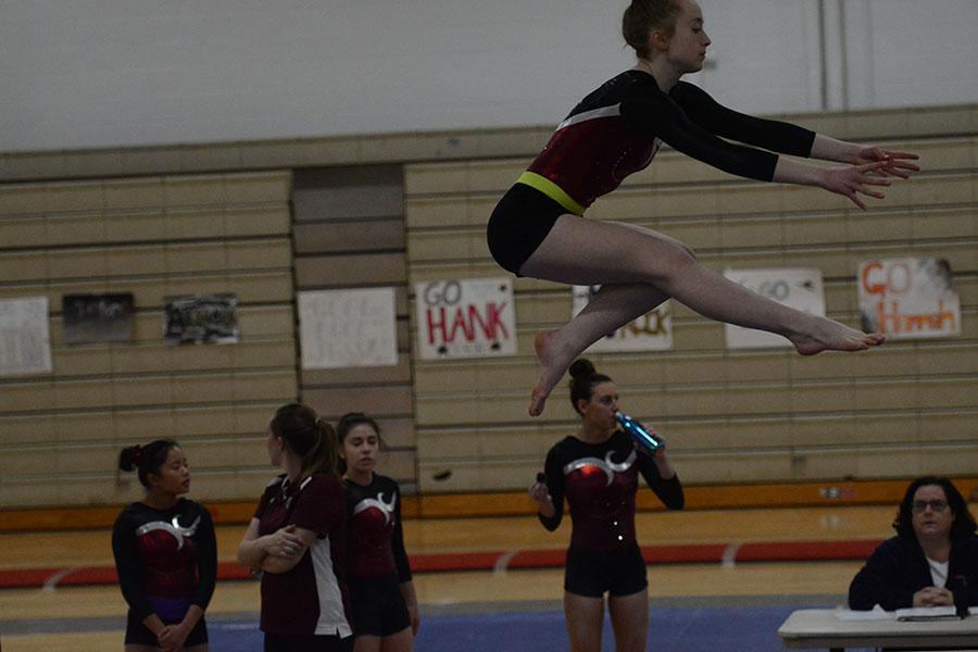 Freshman+Erin+Cragg+doing+a+wolf+jump+on+the+balance+beams.