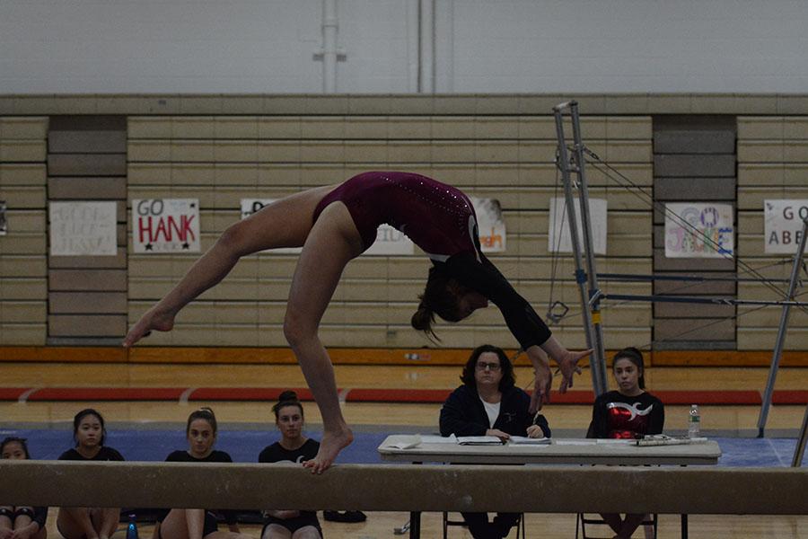 Senior+Jelina+Farrell+doing+a+back+flip+on+the+balance+beams%2C+getting+a+score+8.00