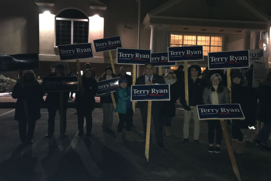 Terry Ryan (Front) with supporters holding signs before the forum.