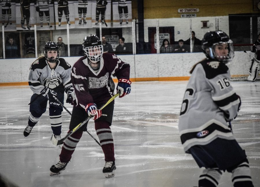 Val+Crory+skates+to+a+stray+puck%2C+with+Vikings+players+following+her+close+behind.