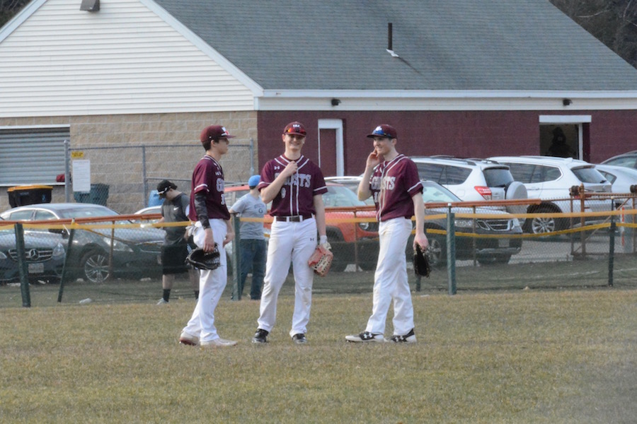Three+junior+outfielders+converse+during+a+pitching+change.