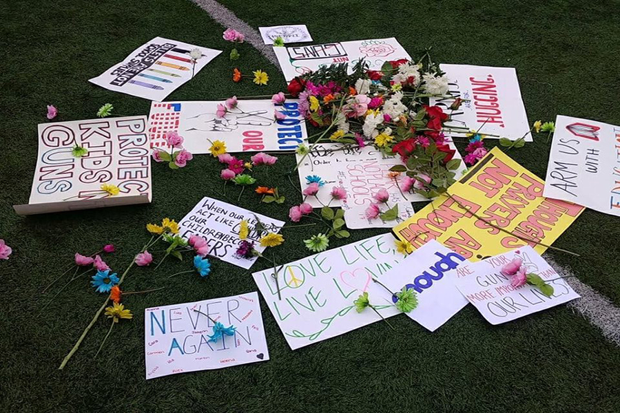 Students+placed+flowers+and+signs+at+the+center+of+the+field.