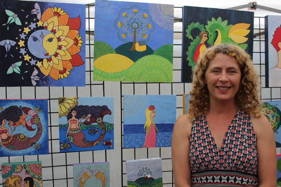 Vendor+Caroline+Sainis+stands+next+to+her+acrylic+folk+paintings.
