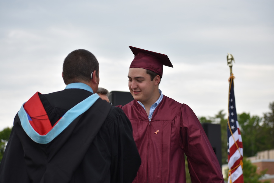 Andrew+Friel+walks+off+stage+after+accepting+his+diploma.