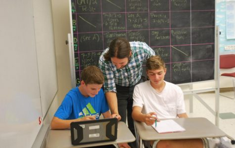Samuel Hummer helps two students in his F Block algebra class.