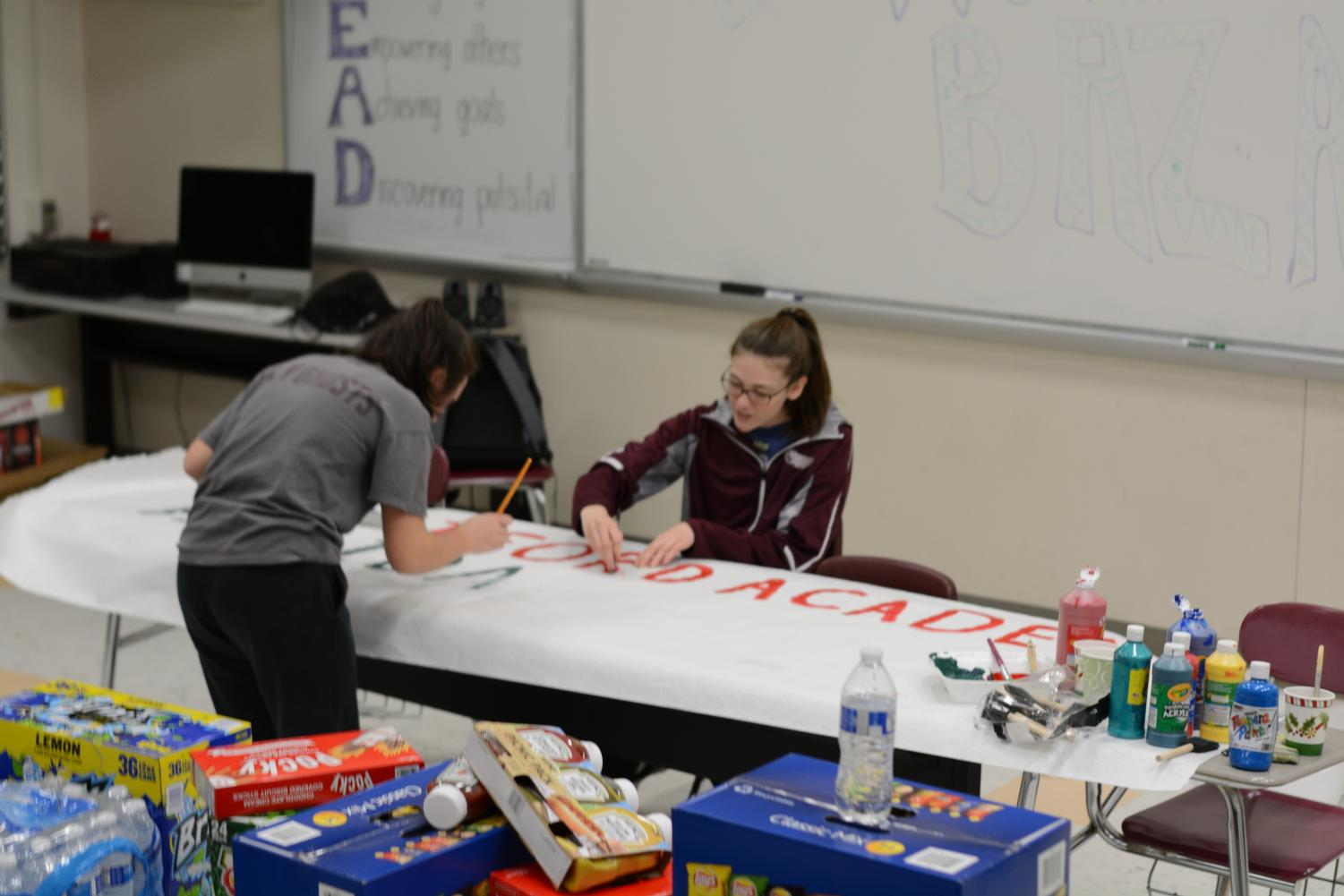 Two+student+council+members+prepare+a+sign+for+the+coming+bazaar.