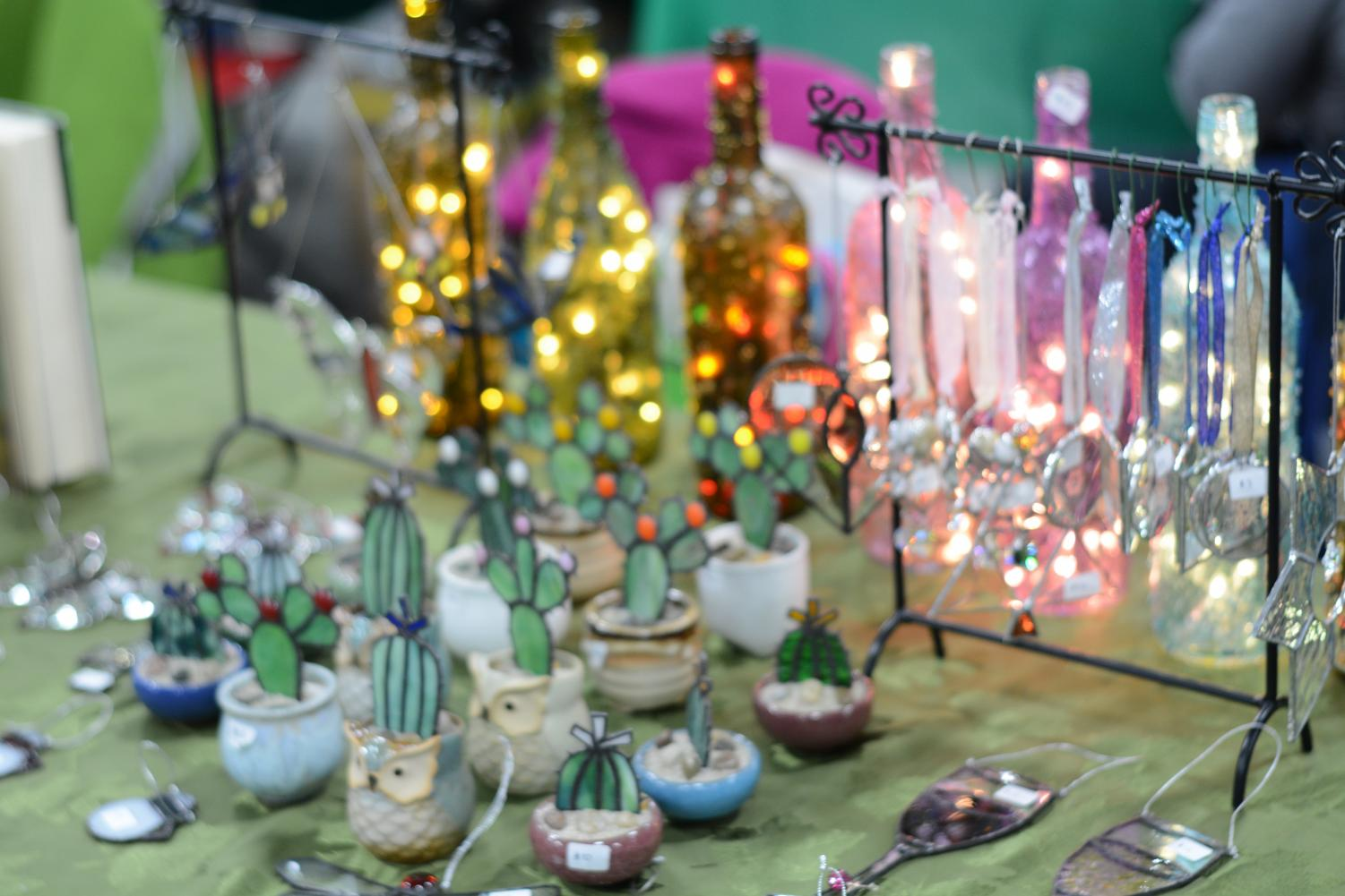 A vendor sets up a display of glass and lights.