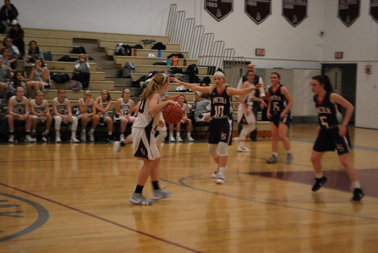 Carly+Davey+dribbles+ball+as+her+teammates+set+up+a+play.