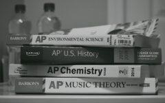AP prep books pile up on a student's desk.