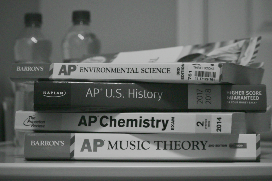 AP prep books pile up on a student's desk.