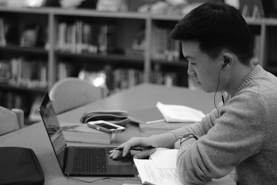 Senior Jun Hong does his homework in the library.