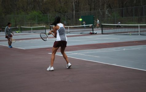 Nithya Sastry preparing to hit the tennis ball back over the net.