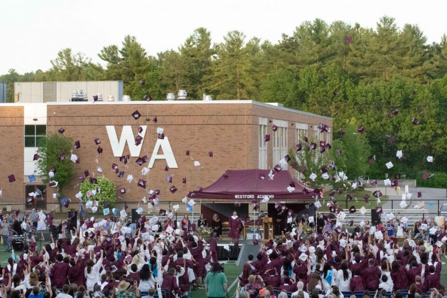 Westford Academy graduates throw their caps in the air to celebrate their graduation