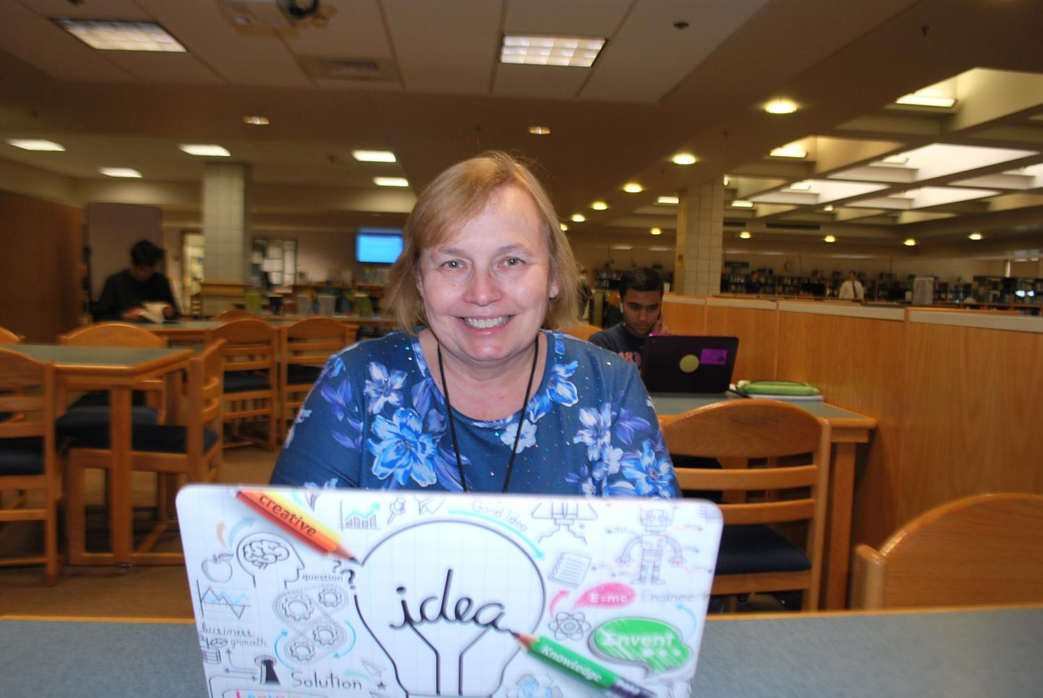 Marianne Butterline poses for a picture in the school library