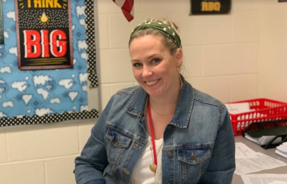 Mrs. Harney poses at her desk in room 148.