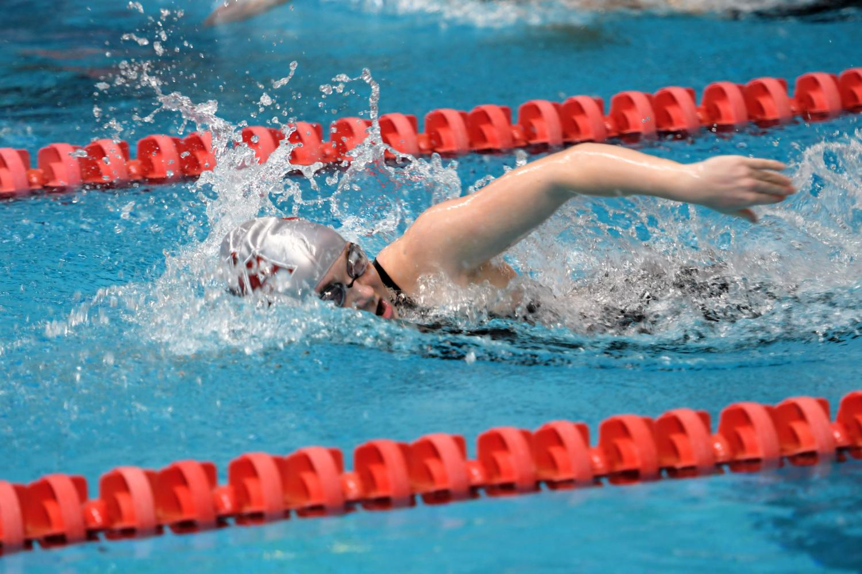 Emily Blatt swimming freestyle at a meet.