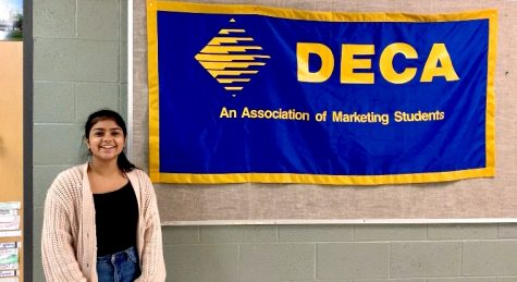 DECA president Shelly Singhal standing next to the DECA board.