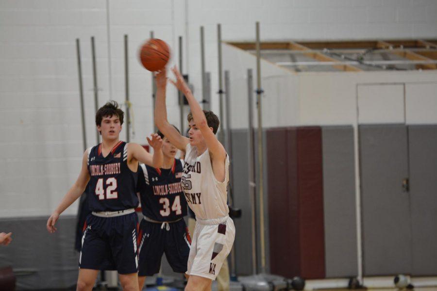 Senior+Jake+Barisano+passing+the+basketball+to+his+team+members.