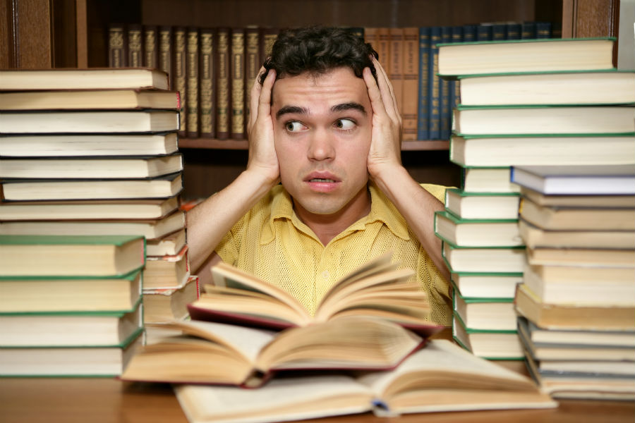 A stressed student is surrounded by textbooks.