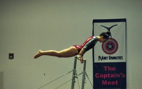 A WA gymnast performs on the uneven bars.