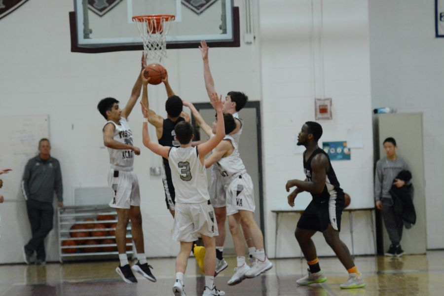 Westford Academy players leap to block a possible point for Cambridge.
