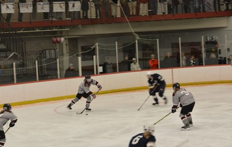 Littleton player Val Crory passes the puck to teammate Brittany Iverson.