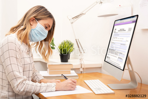 A woman wears a face mask as she works.