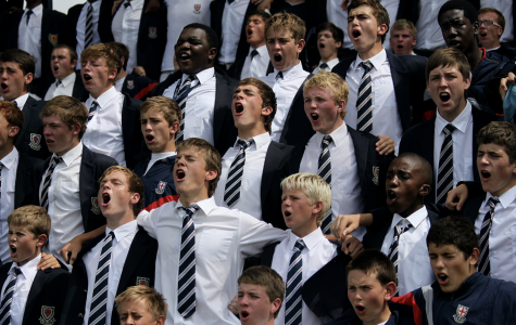 Spirit rages as classmates cheer together in their coordinated uniforms, helping to boost school unity.