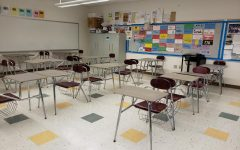 Students' desks are front-facing, separated by a back-facing desk