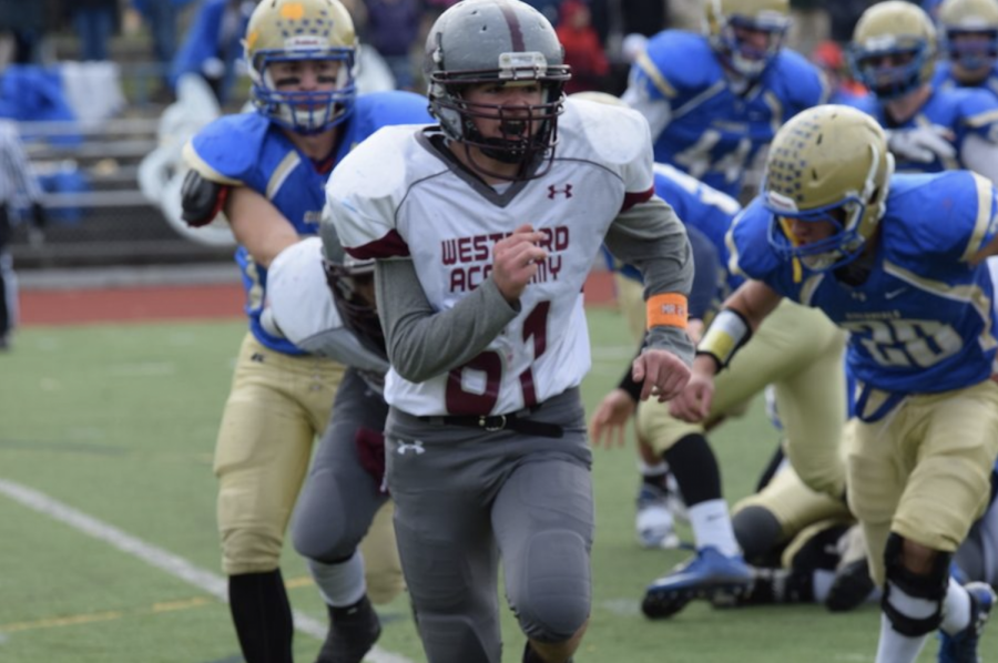 WA Varsity football player being chased by an AB linebacker in the game's first quarter, showing the current Westford Academy uniform.