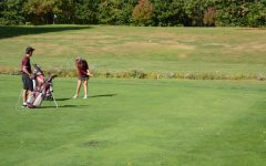 Junior Ryan Smith watches while captain Morgan Smith hits an approach shot onto the first green.